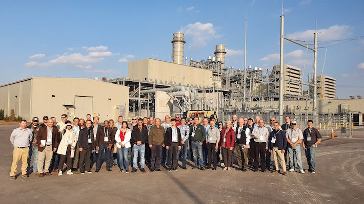 Large tour group standing in front of a power-generation plant